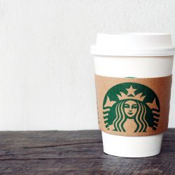 A Starbucks takeaway cup showing the brand label.
